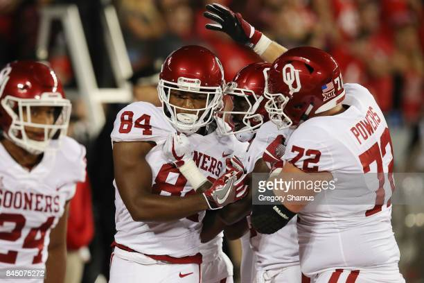 Lee Morris of the Oklahoma Sooners celebrates with teammates after scoring a touchdown on an 18yard reception during the third quarter against the...