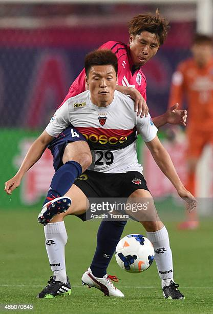 Lee Myung Joo of Pohang Steelers holds off Kota Fujimoto of Cerezo Osaka during the AFC Champions League Group E match between Cerezo Osaka and...