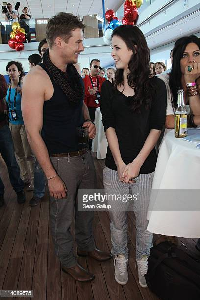 Lee Ryan of the UK band Blue chats with German singer Lena MeyerLandrut of Germany while sailing on a ship on the Rhine River during the Eurovision...