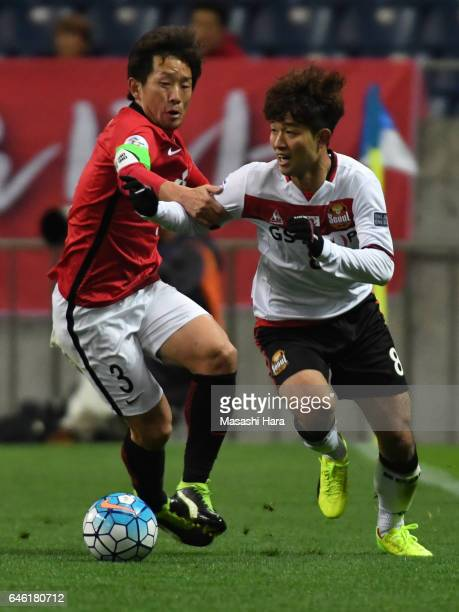 Lee Sangho of FC Seoul and Tomoya Ugajin of Urawa Red Diamonds compete for the ball during the AFC Champions League match Group F match between Urawa...