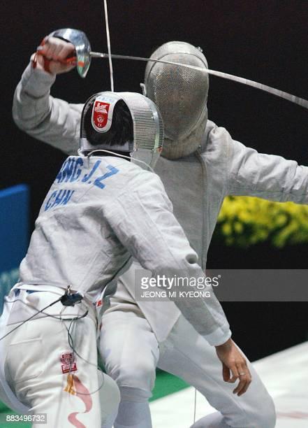 Lee Seung Won of South Korea blocks an attack by Wang Jingzhi of China at the finals of men's fencing sabre individual event at the14th Asian Games...