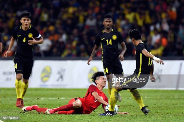 Lee Si Qin of Singapore clashes with Irfan Zakaria of Malaysia during the Men Fooball Group A compettion between Singapore and Malaysia at Shah Alam...