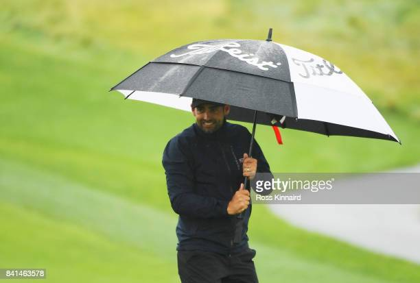 Lee Slattery of England shelters from the rain on the 15th green during day two of the DD REAL Czech Masters at Albatross Golf Resort on September 1...