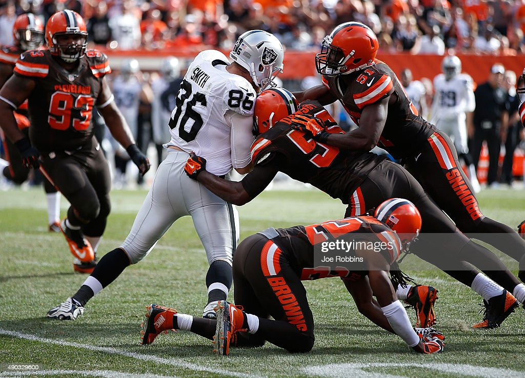 Lee Smith of the Oakland Raiders gets stopped by Karlos Dansby and Barkevious Mingo of the Cleveland Browns during the fourth quarter and at...