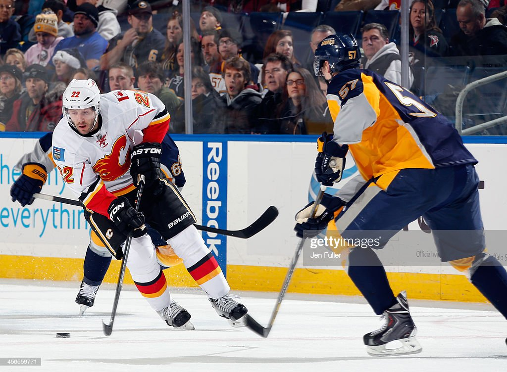 Lee Stempniak #22 of the Calgary Flames controls the puck against Tyler Myers #57 and Tyler Ennis #63 of the Buffalo Sabres at First Niagara Center on December 14, 2013 in Buffalo, New York.