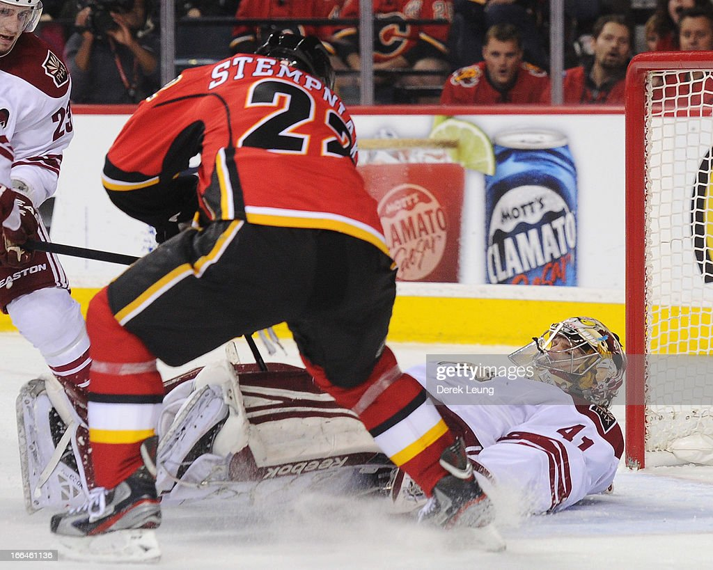 Lee Stempniak #22 of the Calgary Flames digs for the loose puck against goalie Mike Smith #41 of the Phoenix Coyotes who lies prone on the ice during an NHL game at Scotiabank Saddledome on April 12, 2013 in Calgary, Alberta, Canada.