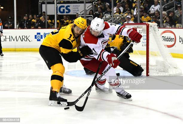 Lee Stempniak of the Carolina Hurricanes fights for the puck with Bryan Rust of the Pittsburgh Penguins at PPG PAINTS Arena on April 2 2017 in...