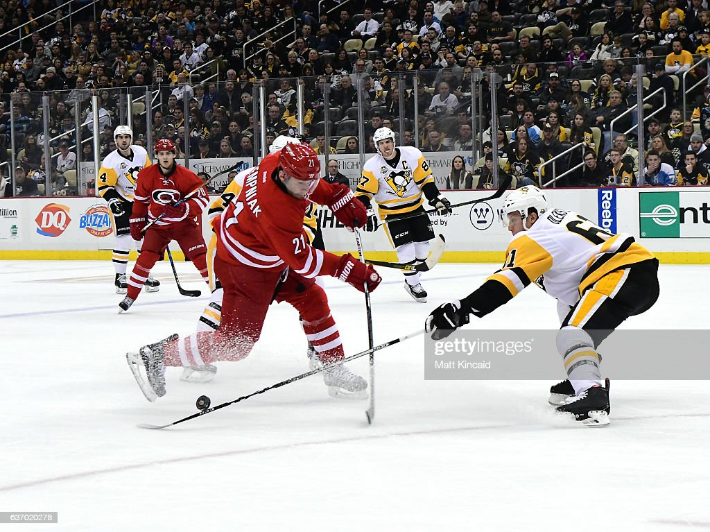 Lee Stempniak #21 of the Carolina Hurricanes tries to shoot the puck as against Steven Oleksy #61 of the Pittsburgh Penguins at PPG PAINTS Arena on December 28, 2016 in Pittsburgh, Pennsylvania.