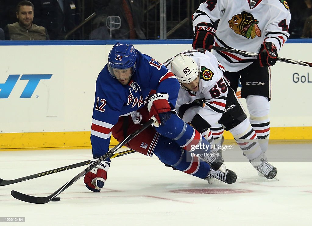 Lee Stempniak #12 of the New York Rangers is tripped up by Andrew Shaw #65 of the Chicago Blackhawks during the third period at Madison Square Garden on October 3, 2014 in New York City. The Rangers defeated the Blackhawks 3-2 in the shootout.