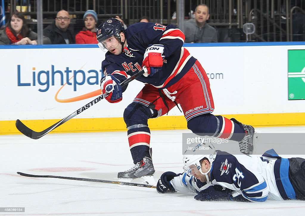 Lee Stempniak of the New York Rangers shoots the puck past Grant Clitsome of the Winnipeg Jets as he attempts to block the shot at Madison Square...