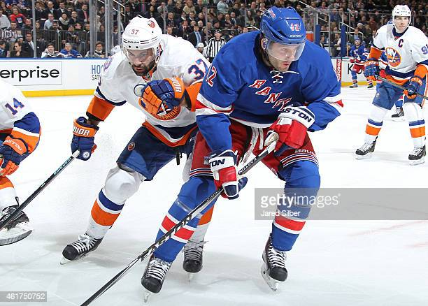 Lee Stempniak of the New York Rangers skates against Brian Strait of the New York Islanders at Madison Square Garden on January 13 2015 in New York...