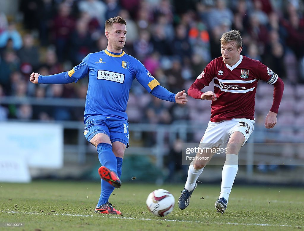 Lee Stevenson of Mansfield Town plays the ball watched by Ricky Ravenhill of Northampton Town during the Sky Bet League Two match between Northampton Town and Mansfield Town at Sixfields on March 15, 2014 in Northampton, England.