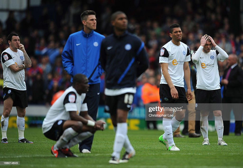 Lee Tomlin (L) and Grant McCann of Peterborough with team mates looks dejected after they are relegated during the npower Championship match between Crystal Palace and Peterborough United at Selhurst Park on May 04, 2013 in London, England.