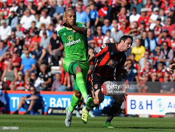 Lee Tomlin of AFC Bournemouth is tackled by Younes Kaboul of Sunderland during the Barclays Premier League match between AFC Bournemouth and...