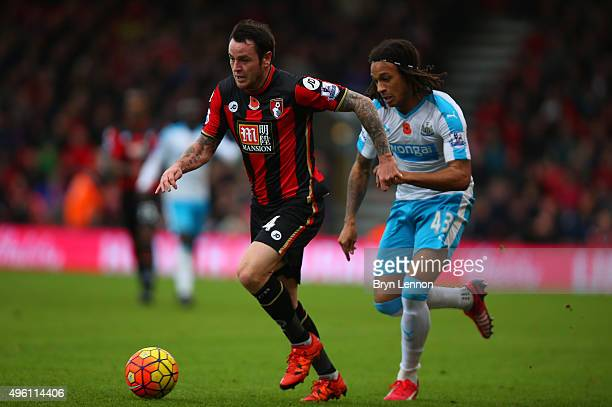 Lee Tomlin of Bournemouth and Kevin Nbabu of Newcastle United compete for the ball during the Barclays Premier League match between AFC Bournemouth...