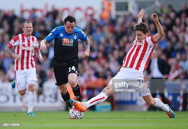 Lee Tomlin of Bournemouth is tackled by Philipp Wollscheid of Stoke City during the Barclays Premier League match between Stoke City and AFC...