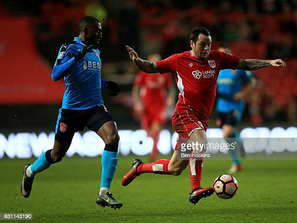 Lee Tomlin of Bristol holds off pressure from Amarii Bell of Fleetwood during The Emirates FA Cup Third Round match between Bristol City and...