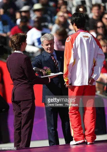 Lee Valley Chief Executive Shaun Dawson presents flowers to Bronze Medalist China's Hewei Dong for the Men's Triple Jump F12 at the Olympic Stadium...