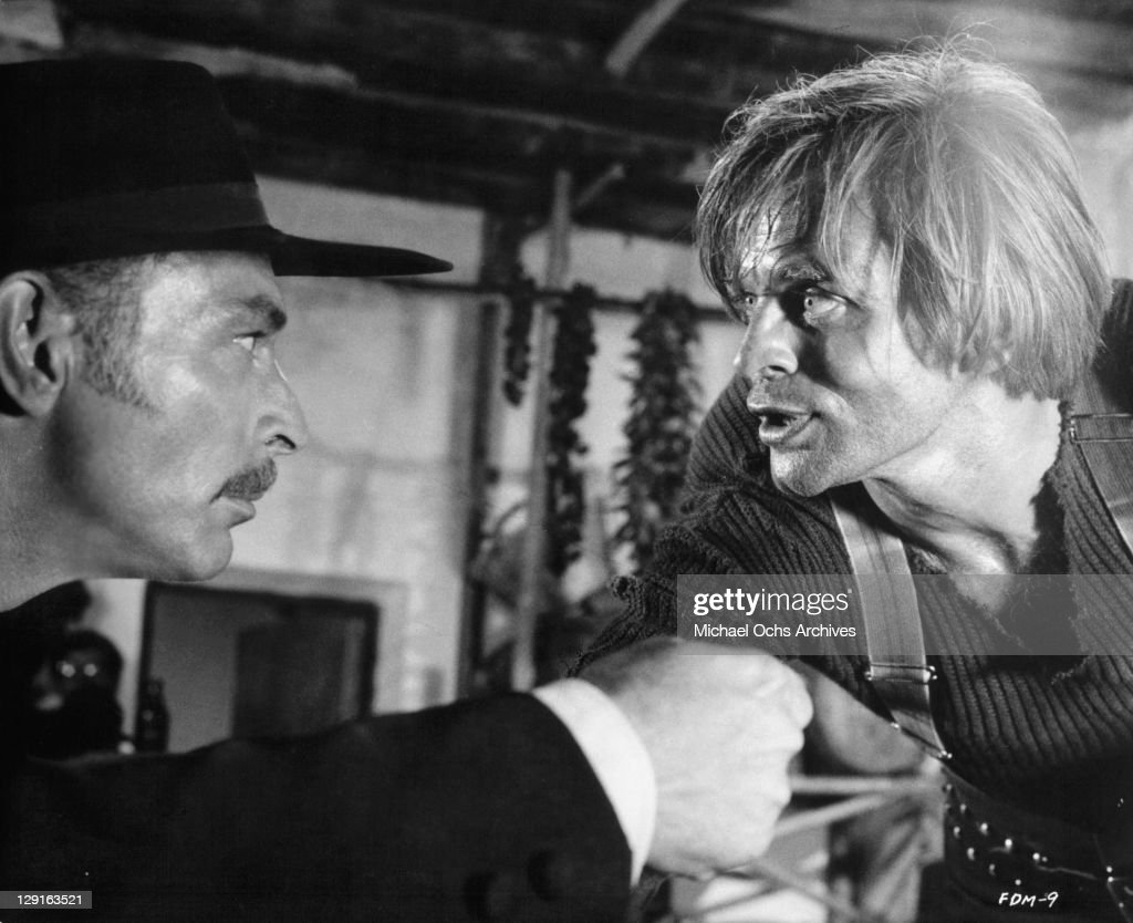 Lee Van Cleef as a bounty hunter, picks a quarrel with Klaus Kinski a criminal in a scene from the film 'For A Few Dollars More', 1965.