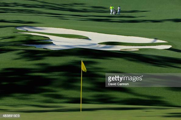 Lee Westwood of England and his caddie Billy Foster stand on the fairway of the 10th hole during the first round of the 2014 Masters Tournament at...