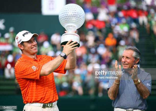 Lee Westwood of England holds the trophy aloft as tournament host Gary Player looks on after the final round of the Nedbank Golf Challenge at the...