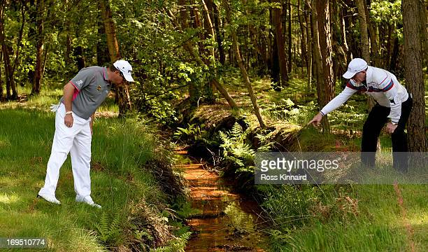 Lee Westwood of England looks for his ball in a water hazard on the twelfth hole during the final round of the BMW PGA Championship on the West...