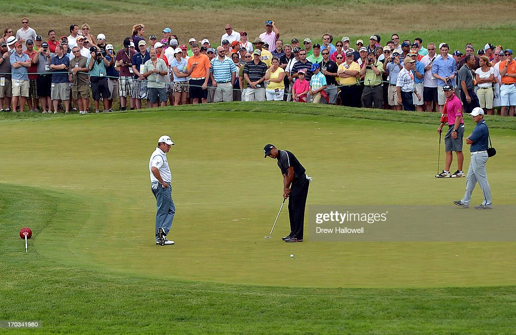 Lee Westwood of England looks on as Tiger Woods of the United States putts during a practice round prior to the start of the 113th U.S. Open at Merion Golf Club on June 11, 2013 in Ardmore, Pennsylvania.