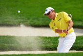 Lee Westwood of England plays a shot from a bunker on the 11th hole during the first round of the 95th PGA Championship on August 8 2013 in Rochester...