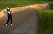 Lee Westwood of England plays out of the 10th greenside bunker during the first round of the Omega Dubai Desert Classic on the Majlis course at the...