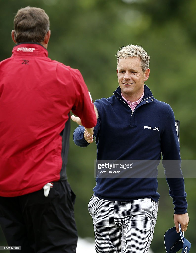 Lee Westwood of England shakes hands with Luke Donald of England on the 18th hole during a continuation of Round One of the 113th U.S. Open at Merion Golf Club on June 14, 2013 in Ardmore, Pennsylvania.
