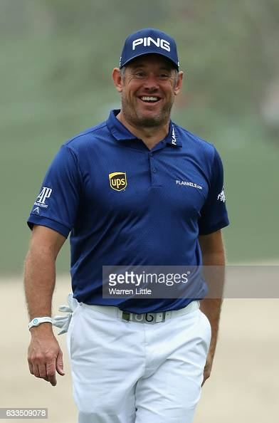 Lee Westwood of England smiles as he runs his ball through the bunker on the 10th hole onto the green during the first round of the Omega Dubai...
