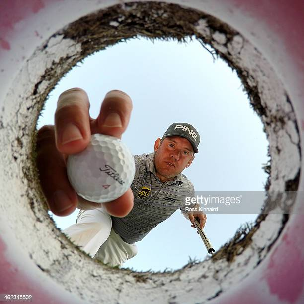 Lee Westwood of England takes a ball out of a golf hole on the putting green during a practice round prior to the Omega Dubai Desert Classic at the...