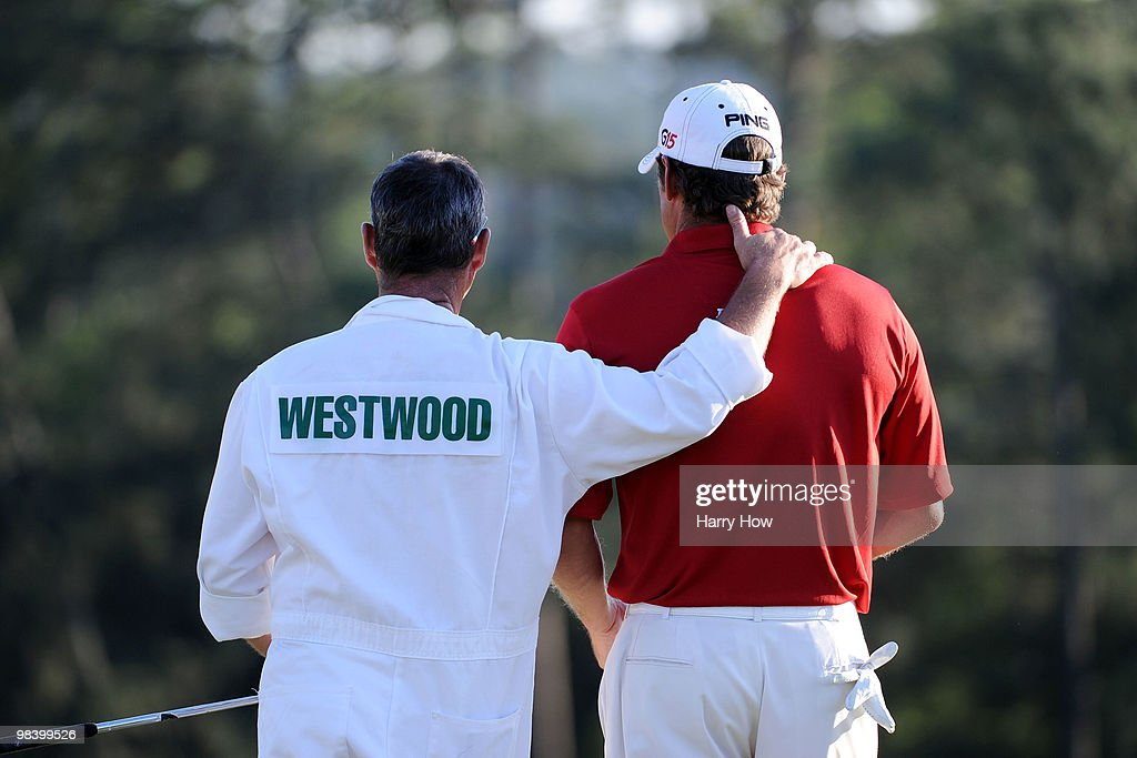 Lee Westwood of England waits with his caddie Billy Foster on the 18th green during the 2010 Masters Tournament at Augusta National Golf Club on April 11, 2010 in Augusta, Georgia.
