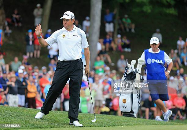 Lee Westwood of England waves after chipping in for par on the second hole as caddie Billy Foster looks on during the second round of the 96th PGA...