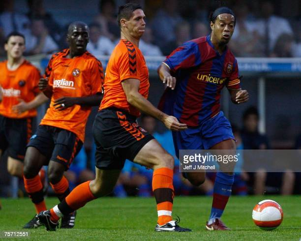 Lee Wikie of Dundee United tackles Ronaldinho of Barcelona during their friendly match between Dundee United and Barcelona at Tannadice Stadium on...