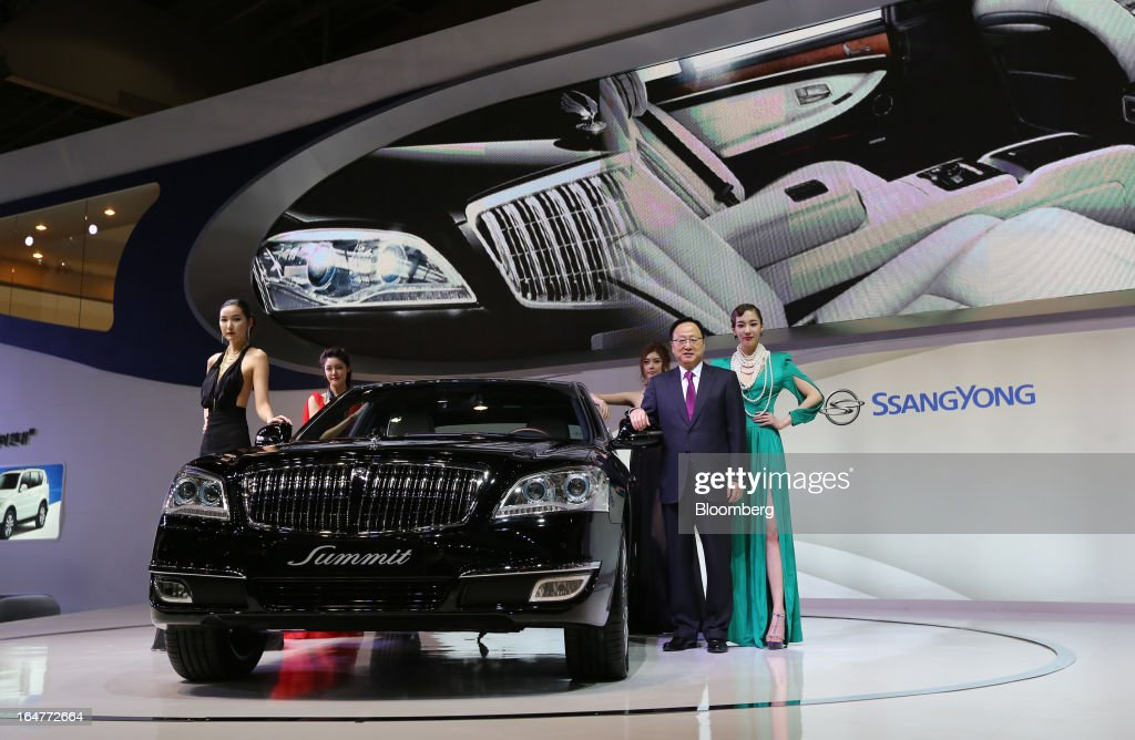 Lee Yoo Il, chief executive officer of Ssangyong Motor Co., second right, poses for a photograph next to the company's Chairman Summit luxury vehicle during the press day of the Seoul Motor Show in Goyang, South Korea, on Thursday, March 28, 2013. The show runs from today until April 7. Photographer: SeongJoon Cho/Bloomberg via Getty Images