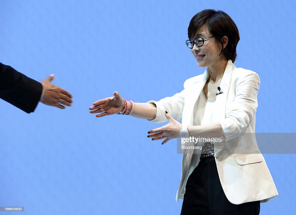 Lee Young Hee, executive vice president for the mobile business at Samsung Electronics Co., right, shakes hands with a guest speaker during the Galaxy S4 World Tour 2013 Tokyo event in Tokyo, Japan, on Thursday, May 16, 2013. Samsung Electronics reported a record quarterly profit in April for the three months ended March 31. Photographer: Tomohiro Ohsumi/Bloomberg via Getty Images