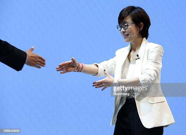 Lee Young Hee executive vice president for the mobile business at Samsung Electronics Co right shakes hands with a guest speaker during the Galaxy S4...