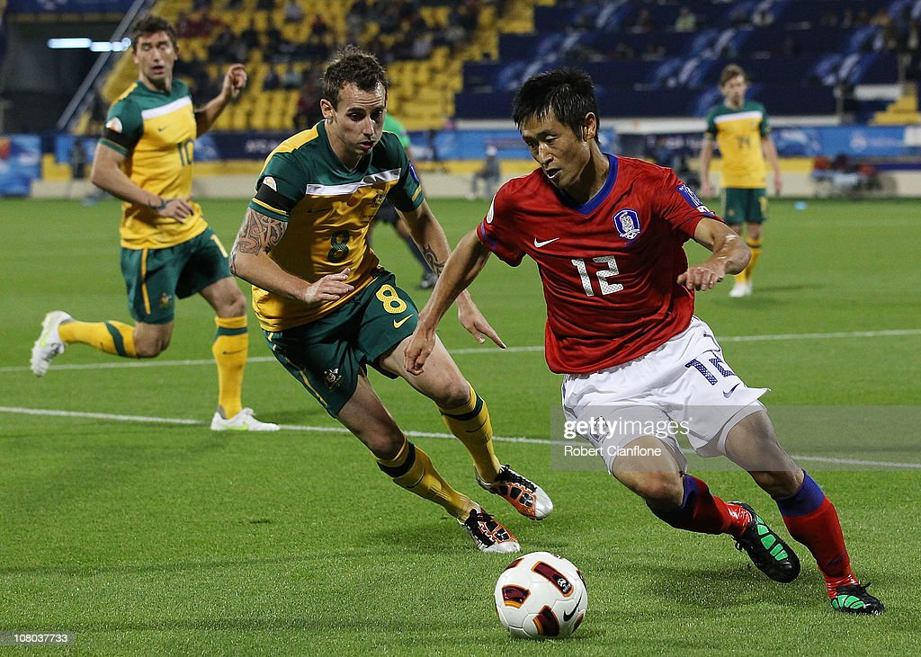 Lee Young Pyo of Korea is chased by Luke Wilkshire of Australia during the AFC Asian Cup Group C match between the Australian Socceroos and Korea...