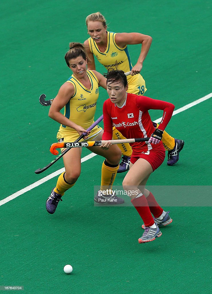 Lee Young Sil of Korea runs onto the ball against Jane Claxton and Kellie White of Australia during the International Test match between the Australian Hockeyroos and Korea at Perth Hockey Stadium on April 27, 2013 in Perth, Australia.