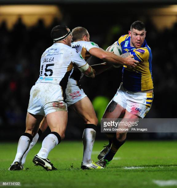 Leeds Rhinos' Brett Delaney is tackled by Hull FC's Ben Galea and Daniel Holdsworth during the Super League match at Headingley Carnegie Stadium Leeds