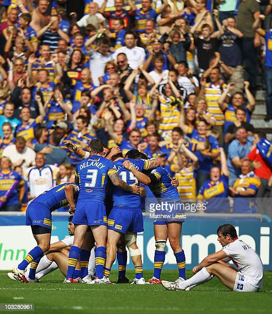 Leeds Rhinos celebrate their teams win as Paul Wellens of St Helens looks on during the Carnegie Challenge Cup Semi Final match between Leeds Rhinos...