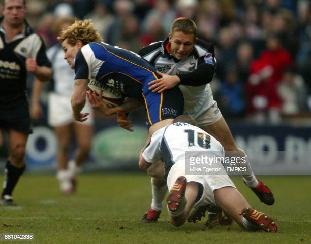 Leeds Tykes' Matt Cardey is tackled by Newcastle Falcons' Jonny Wilkinson and Dave Walder
