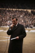 Leeds United football manager Don Revie speaking into a microphone before the start of a match