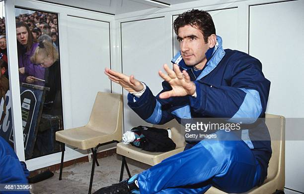 Leeds United forward Eric Cantona calms the media down as he looks on from the bench prior to making his Leeds debut as a substitute during the...