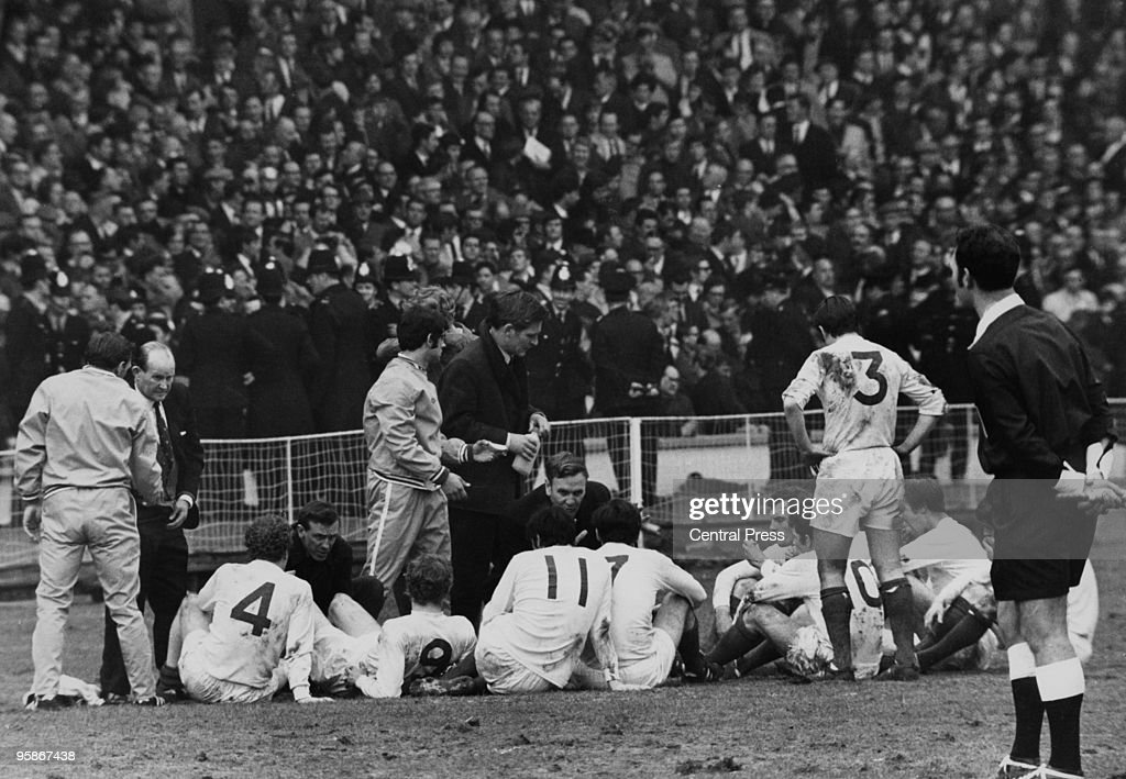 Leeds United manager Don Revie (centre, kneeling) gives a pep talk to his exhausted team before extra time during the FA Cup Final between Leeds and Chelsea at Wembley, 11th April 1970. The match ended in a 2-2 draw, with a replay at Old Trafford on the 29th. Among the Leeds players are Billy Bremner (left), Mick Jones, Eddie Gray, Peter Lorimer (in front of Revie), John Giles, Terry Cooper (number 3, standing) and Jackie Charlton.
