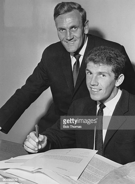Leeds United manager Don Revie looks on as Irish footballer Johnny Giles signs for the club July 1963