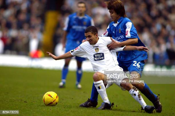 Leeds United's Aaron Lennon is held back by Cardiff City's Junichi Inamoto