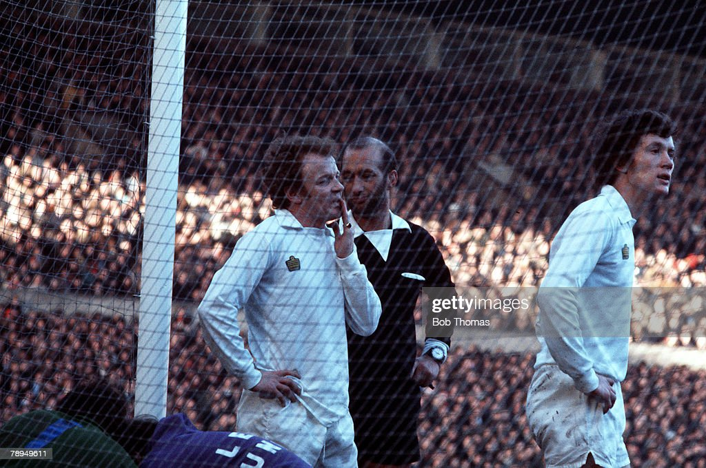Leeds United's captain Billy Bremner is spoken to by the referee, with teammate Trevor Cherry close by