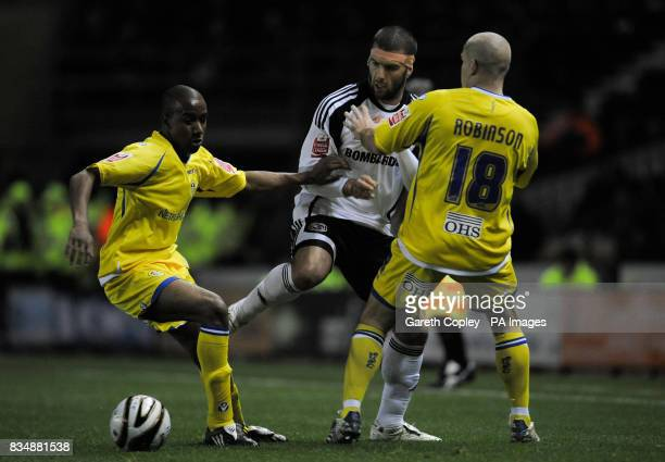 Leeds United's Fabian Delph and Andy Robinson tackle Derby's Emanuel Villa during the Carling Cup Fourth Round match at Pride Park Derby